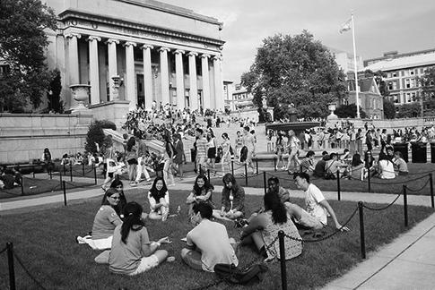 Roughly a dozen students sit in a circle on a grassy patch near the steps of Low Memorial Library on a bright, sunny day