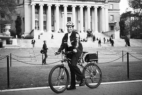 A female public safety officer straddles a bicycle on College Walk with Low Library in the background on a sunny day